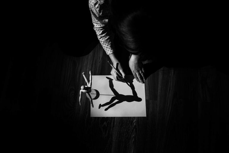 Child tracing a shadow on paper in black and white