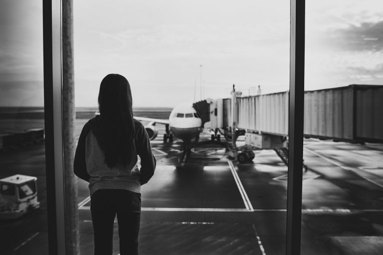 little girl looking out window to first plane ride
