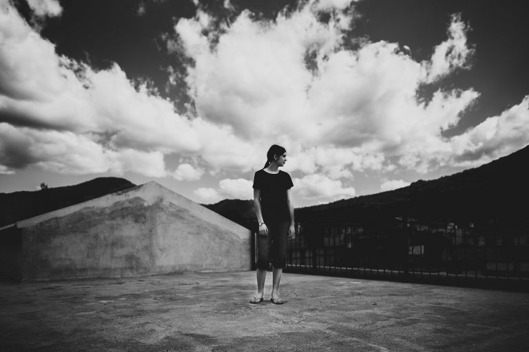 teenager in black and white standing in front of huge clouds on a roof