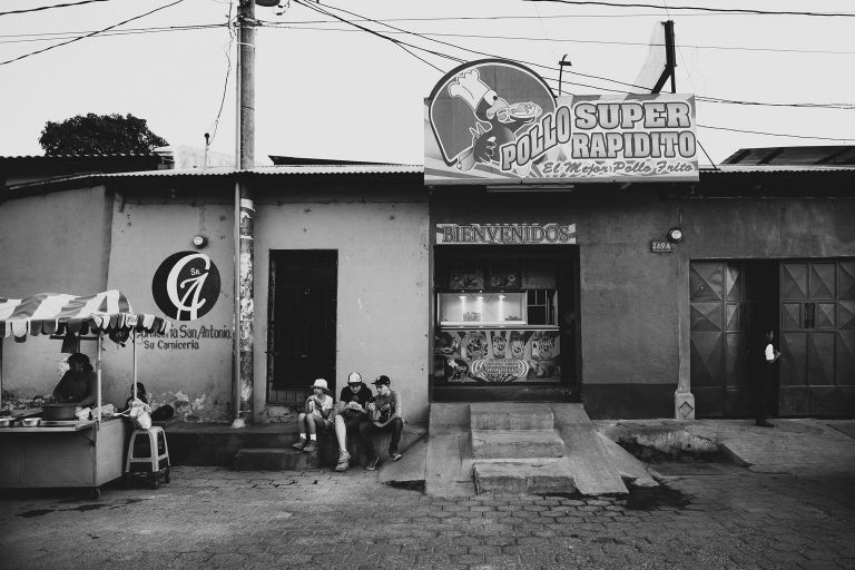 kids eating fried chicken on a curb in guatemala