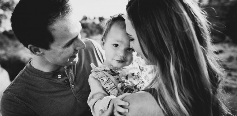 photo of baby looking into camera while parents are holding her
