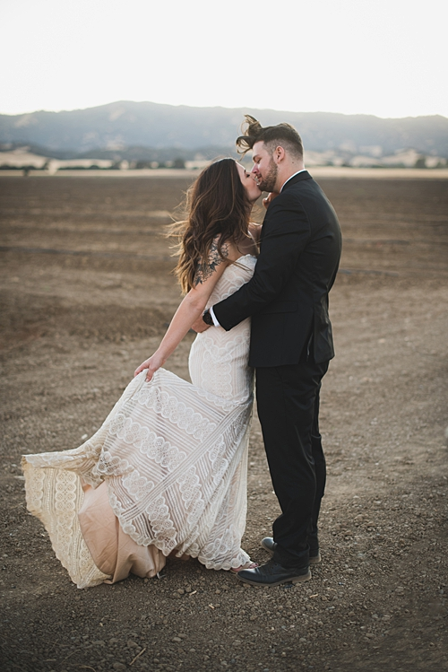photo of bride and groom kissing in the wind