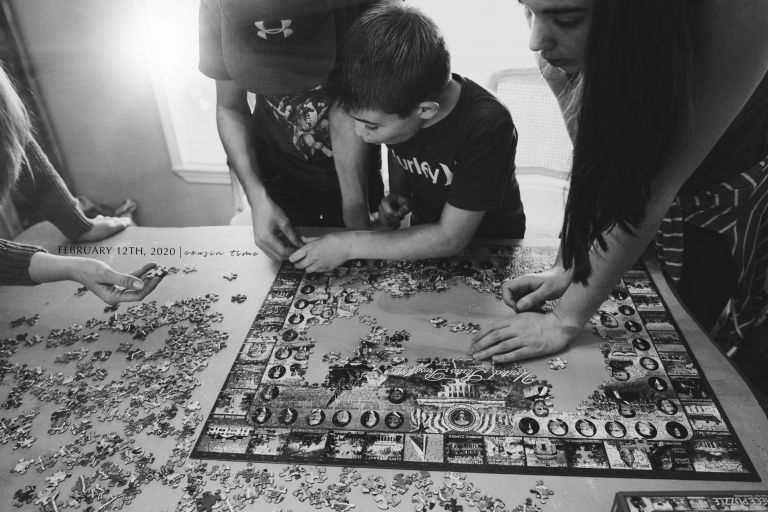 Black and white photo of children putting together a puzzle